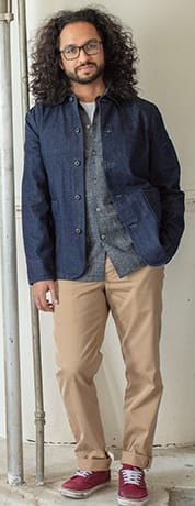 A guy with long hair wearing a stylish denim light-weight jacket, button up blue shirt, and tan pants.