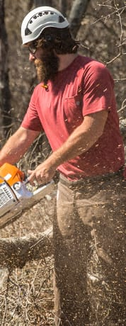 A landscape worker wearing a red shirt, brown pants, and a helmet, using a chain saw.
