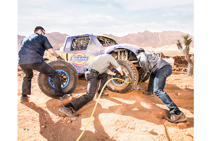 FLEX Tough Max™ Twill Work Pants (DP800) and Denim Jeans (DP802) in rally car lifestyle image